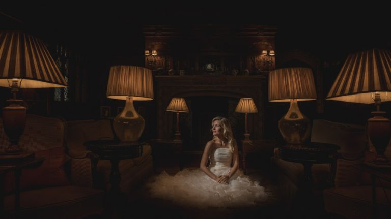 Using LED lighting at weddings, a bridal model looks towards and LED light during a wedding photography training course