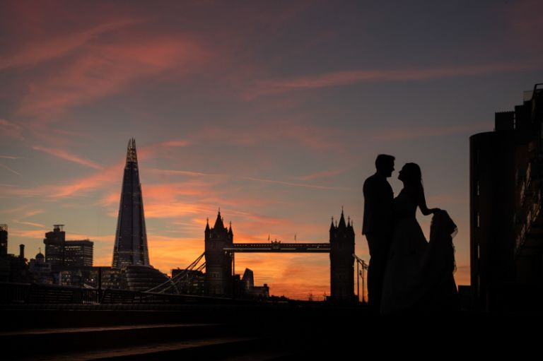 Bride and groom silhouettes with London skyline behind. The Shard and Tower Bridge